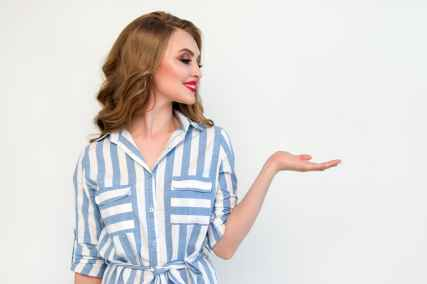 woman in blue and white striped top raising her left hand